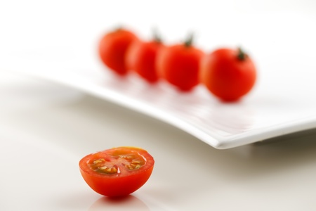 Four fresh organic tomatoes on a white ceramic plate and a half of tomato in the foreground Stock Photo - 22169974