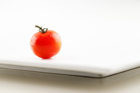 A fresh organic tomato with water droplets on a white ceramic plate Stock Photo - 22169975