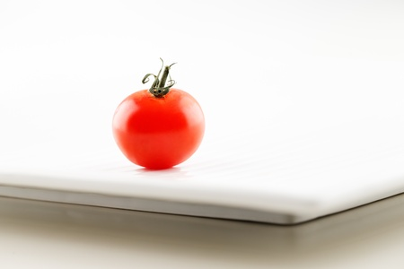 A fresh organic tomato with water droplets on a white ceramic plate Stock Photo - 22169976