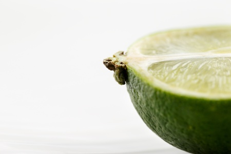 A portion of a fresh organic lime shot in a creative abstract manner against a white background Stock Photo - 22169872