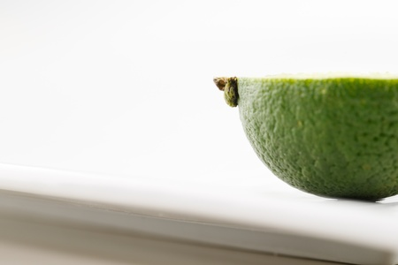 A portion of a fresh organic lime shot in a creative abstract manner against a white background Stock Photo - 22169873