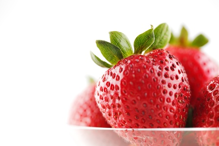 A bowl of organic fresh strawberries on a white background Stock Photo - 22169817