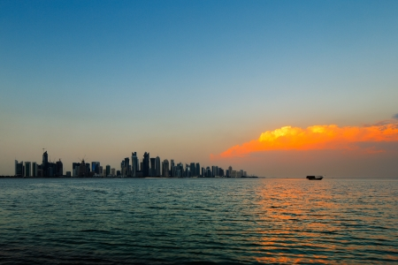 adds: Doha, Qatar  A beautiful sunset cloud adds vibrancy to the city skyline Stock Photo