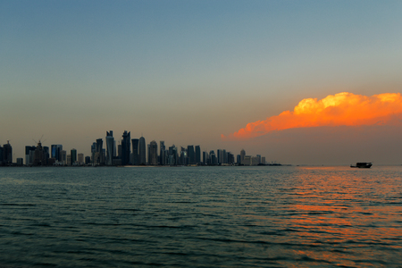 Doha, Qatar  A beautiful sunset cloud adds vibrancy to the city skyline Stock Photo - 24928241