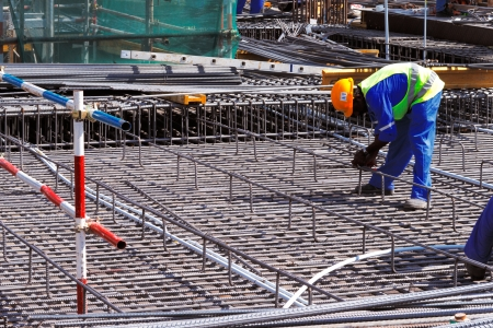 reinforcing bar: A steel fixer carefully tying reinforced steel bars in position in preparation for the construction of a concrete slab