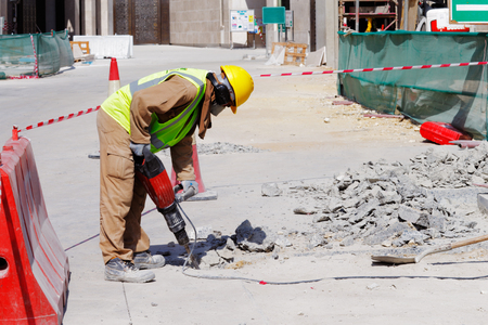 A laborer is well protected in safety gear as he uses a jackhammer to break up a reinforced concrete pavement