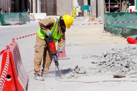 Een arbeider is goed beschermd in veiligheid vistuig als hij gebruik maakt van een drilboor te breken van een gewapend betonnen bestrating