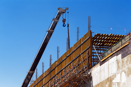 A mobile crane is poised to lift reinforced concrete shuttering