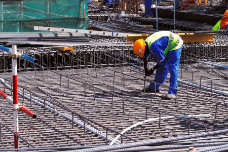 concrete structure: A steel fixer carefully tying reinforced steel bars in position in preparation for the construction of a concrete slab