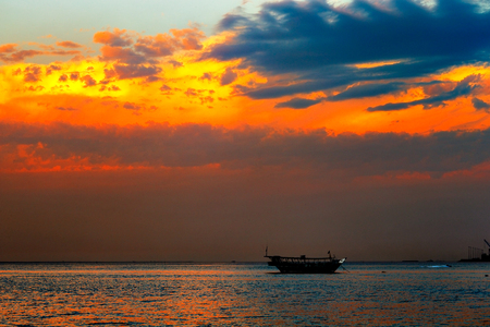 Doha, Qatar  A Dhow is anchored in West Bay as the sunset sky becomes vibrant with contrasting colour photo