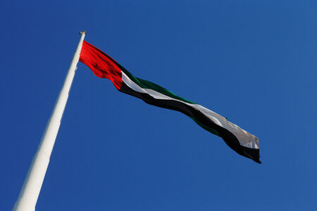 uae: Abu Dhabi, UAE  A skyward view of the UAE National Flag as it blows beautifully in the wind Stock Photo