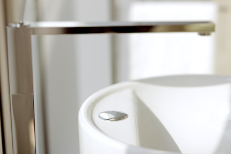 An abstract detail of a contemporary wash-hand basin and faucet photo