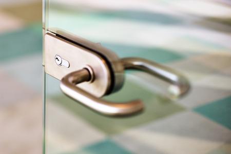 Een abstract detail van een hedendaagse deurklink voor een glazen deur