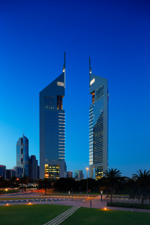 emirates: A profile of the iconic Emirates Towers in Dubai, UAE at dusk as viewed from DIFC, the financial hub of Dubai