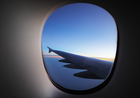 A window view of the wing of a modern luxury jet plane at dawn Stock Photo