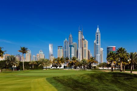 Dubai, UAE  A cityscape view of Dubai Marina from a nearby lush green golf course
