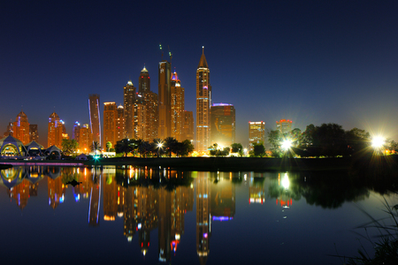 Dubai, UAE  A cityscape view of Dubai Marina at dusk and it s reflection on a nearby lake photo