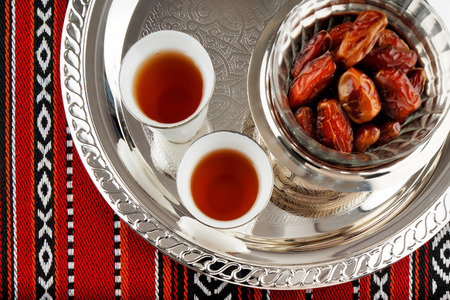 coffee pot: Iconic Abrian fabric is graced with symbols of Arabia, in particular Arabic tea and dates, they symbolise Arabian hospitality. Stock Photo