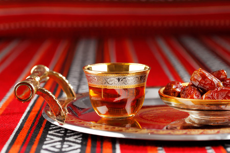 quran: Iconic Abrian fabric is graced with symbols of Arabia, in particular Arabic tea and dates, they symbolise Arabian hospitality. Stock Photo