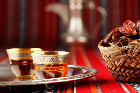 arabic: Iconic Abrian fabric is graced with symbols of Arabia, in particular Arabic tea and dates, they symbolise Arabian hospitality. Stock Photo