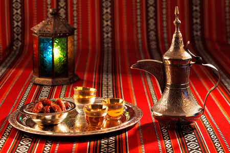 アラビア、特にアラビア語茶および日付の記号と象徴的な Abrian 生地を飾って、アラビア式のホスピタリティを象徴します。 写真素材