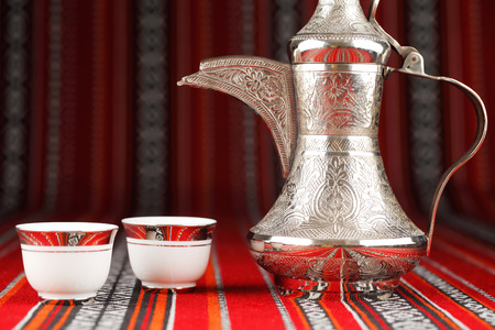 Ornate Arabian tea cups and a dallah are placed on traditional red fabric from the Gulf region. Фото со стока