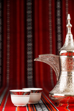 Ornate Arabian tea cups and a dallah are placed on traditional red fabric from the Gulf region. Stock Photo