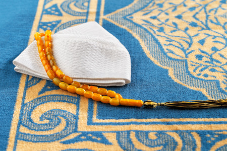 recite: The Masbaha is also known as Tasbih is a string of prayer beads which is traditionally used by Muslims along with the Quran Stock Photo