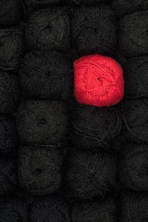Black and red balls of wool, gold knitting industry Фото со стока