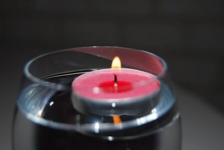 Pink candle in a glass of water, light dark background, light, flame candlelight