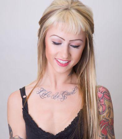 tattoed: Tattoed mujer joven mirando hacia abajo con una sonrisa