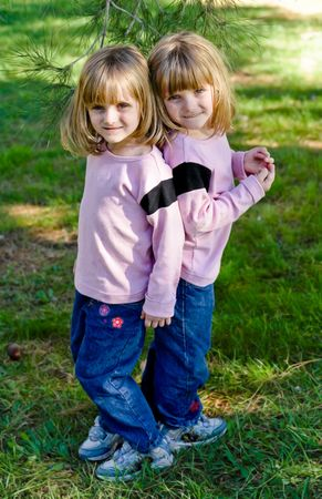 twin sister: Twin little girls in the park under a pine tree Stock Photo