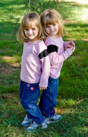 gemelas: Twin ni�as en el parque bajo un �rbol de pino