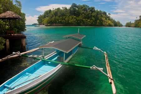 sulawesi: A traditional fishing boat or jukung with outriggers at the Togean Islands, Sulawesi, Indonesia Stock Photo