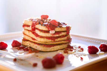 Homemade raspberry pancakes sprinkled with peanuts served for breakfast. Gluten-free diet. Gourmet Meal. American cuisine.