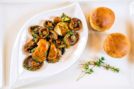 Fried mushrooms with basil. Served with buns. Decorated with thyme. Delicious snack. French cuisine. Top view.
