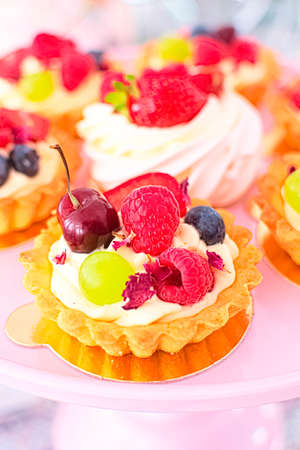 Tartlets with custard and decorated with assorted kind of fresh fruit. French cuisine. Gourmet dessert. Perfect for any occasion, incl. birthday party.