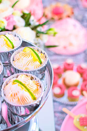 Lime cheesecakes with meringue topped with a fresh slice of lime. Composition with flowers in the background. Gourmet dessert. Perfect for any occasion, incl. birthday party. Zdjęcie Seryjne