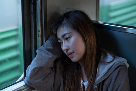 topcoat: Young woman looks sad in the train Stock Photo