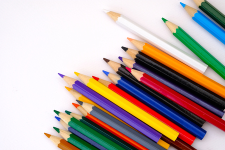 navy blue background: colored pencils in a parellel pattern on white background Stock Photo
