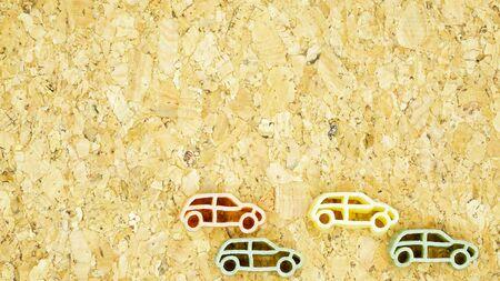car shape pasta arranged in pattern on a cork board