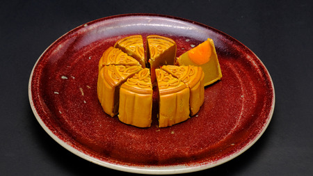 moon-cake, a traditional chinese pastry, eaten during the harvest moon festival in october, is composed of durian, sweet bean and almond slices fillings, with preserved duck york in the center, is placed on a red cceramic plate Stock Photo