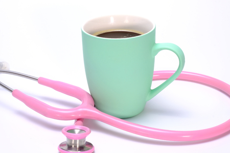 a pink stethoscope and a mug of hot coffee isolated on white background