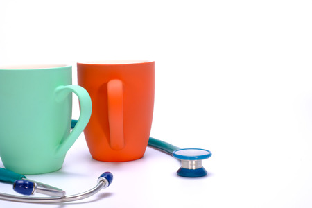 a green stethoscope and two green and  orange coffee mugs on white background Stock Photo