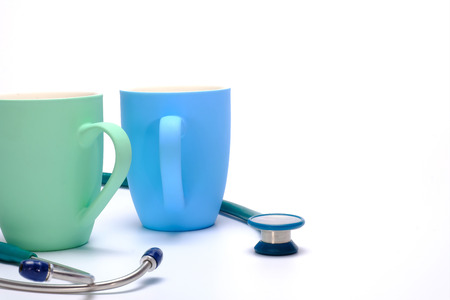 a green stethoscope and two colorful coffee mugs on white background Stock Photo