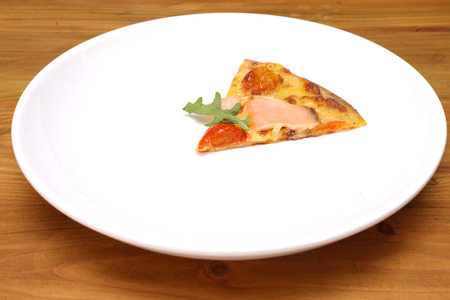 a thin slice of pizza, on a white plate Stock Photo
