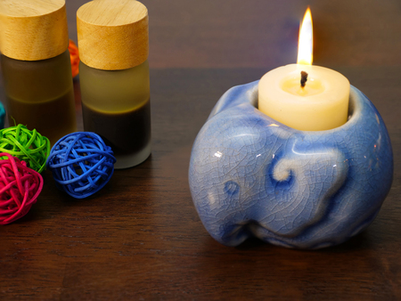 ceremic: white candle and blue elephant shape candle holder with bottles of aromatherapy oil, on dark natural wood background Stock Photo