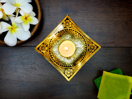 Top view of white candle, gold pattern lacquerware, bars of herbal spa soap, and bowl of white tropical flowers on dark natural wood background