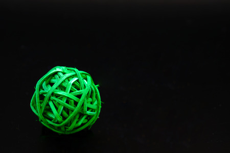 a ball of green rattan for decoration on black background