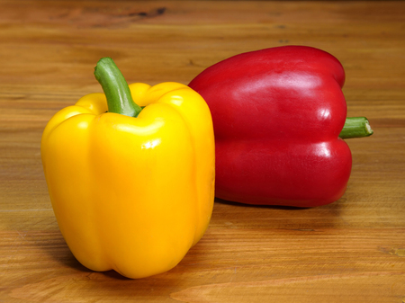 fresh, large and colorful bell peppers in red and yellow on a wooden background Stock Photo